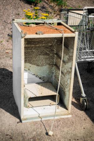 Ett gammalt kylskåp står öppet på marken utomhus. Man kan se lera inne i kylskåpet, som tyder på att det legat i en bäck.