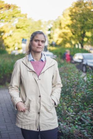 En bestämd kvinna. I bakgrunden träd och buskage.