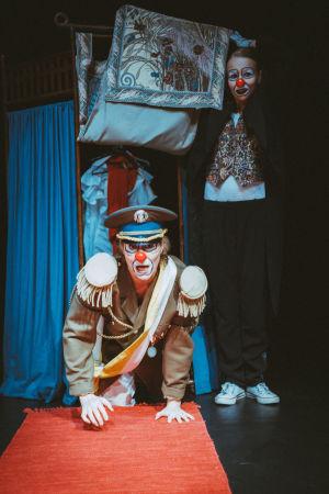 Diktaattorin univormuun pukeutunut Babylon-klovni kontillaan maassa, takana seisoo Re-klovni.