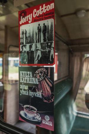 Kaksi vanhaa mainosta junanvaunun oven ikkunalasissa.