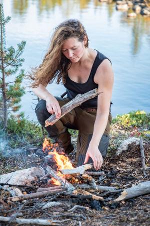 En kvinna lägger ved på en brasa utomhus. I bakgrunden syns en sjö.