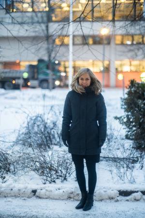 En kvinna står i en snöig stadsmiljö. Hon ser glad ut.