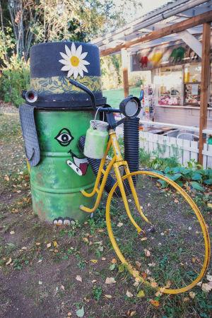 Muun muassa öljytynnyristä ja vanhasta polkupyörästä tehty norsupatsas pihamaalla, taustalla kioski.