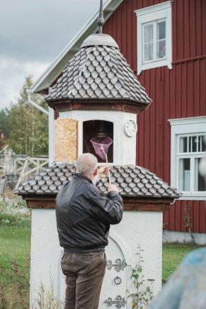Mies soittaa perhoshaavin avulla pienessä kellotapulissa olevaa kirkonkelloa.
