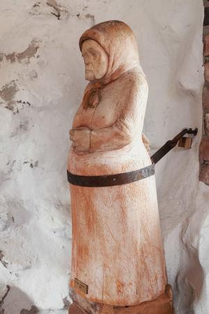 Puusta veistetty vaivaisakka, joka on kiinnitetty rautalukolla seinään.