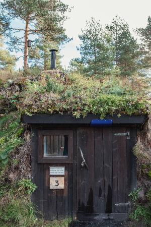 Maan sisään rakennettu mökki, tumma ovi, katolla sammalta ja ruohoa, savupiippu