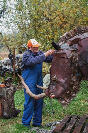 Mies tekee suurta, jätemateriaalista tehtyä villasarvikuono-veistosta.