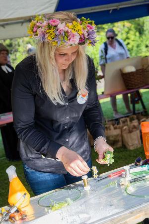 Floristmästaren Nelly Koitto med en blomstarkrans i sitt hår arbetar med små snittblommor.
