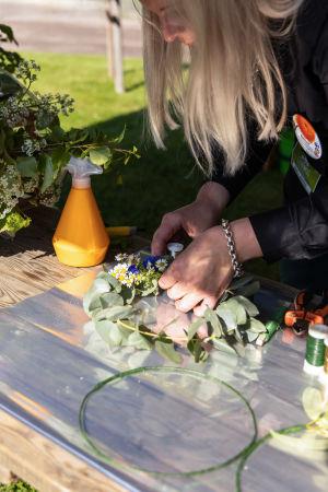 Närbild av en floristmästares händer som binder en blomsterkrans av eukalyptus, blåklint och prästkrage.