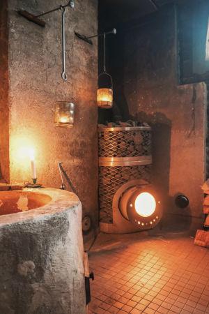 Kiuas, jossa palaa tuli, ja kynttilöitä saunassa.
