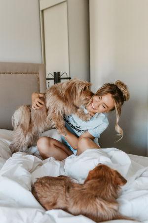Therese Lindgren i en säng med hundar.