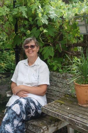 En dam sitter på en bänk ute i en trädgård och ler.
