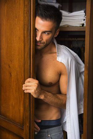 Lättkläd man tittar ut ur garderob