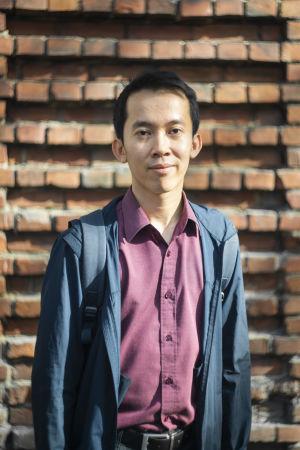 En man står framför en tegelvägg. Han ser in i kameran. Han har ett neutralt ansiktsuttryck men ser helt nöjd ut. På sig har han en röd kragskjorta och på den en blå jacka.
