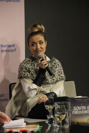 På bilden syns den isländska författaren Thordis Elva tala i en mikrofon när hon intervjuas om sin bok på scen.