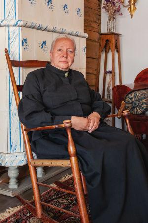 Kvinna i vitt hår med knut i nacken och helsvart ylleklänning sitter i gungstol framför en kakelugn.