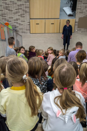 Morgonsamling, i förgrunden elever som sitter med ryggarna vända mot kameran i en trappa, rektorn står längst ner