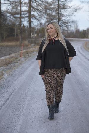 En blond kvinna går på en grusväg ute på landet.