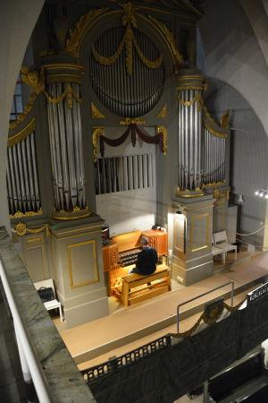 En man spelar på en stor kyrkorgel.
