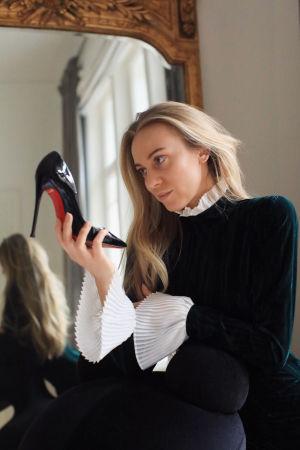 På bilden syns influeraren Sandra Hagelstam som håller i och tittar på en svart högklackad sko med röd sula.