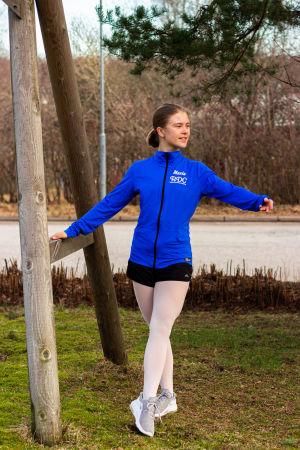 En ung kvinna i blå sportjacka och vita trikåer gör en balettrörelse (tendu) utomhus. Tar stöd av en stolpe