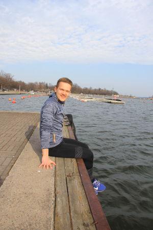 Oscar Holmström iklädd träningskläder sitter på en bryggkant.