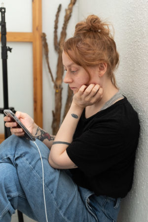 Hilla Kurki läser en artikel på sin telefon, 7.5 Vallgård
