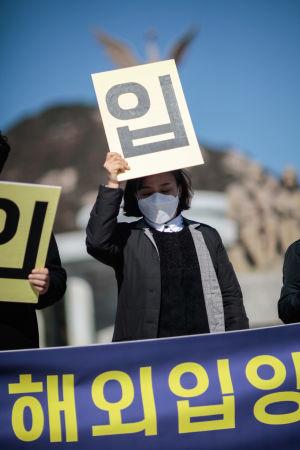 En kvinna med munskydd håller upp en skylt med koreanska tecken.