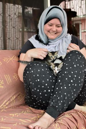 Marina Lischi istuu kissanpennut sylissään sohvalla.