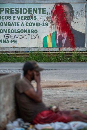 Ett vandaliserat plakat som föreställer president Jair Bolsonaro. Protest mot hans hantering av pandemin i Brasilien.
