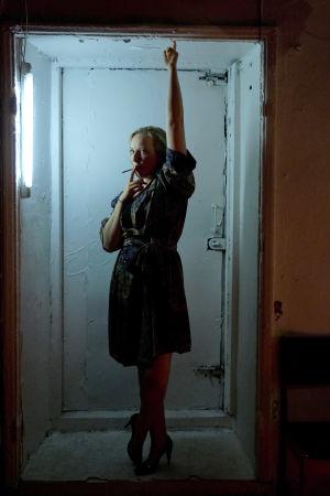 Milla Kankaan näyttelemä Sarah poltaa savuketta hämärässä porttikongissa.