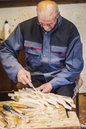 Snickaren och konstnären Leo Karppanen snider en figur i trä.