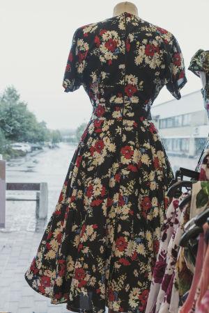 Blommig klänning i skyltfönster, i bakgrunden en grådaskig gatubild.