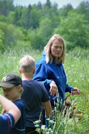 Anki Nyberg leder barn genom en äng för att hitta örter