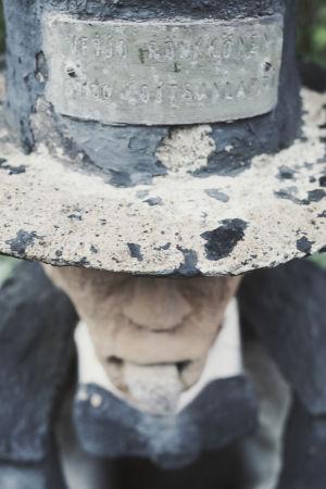 """Staty med cylinderhatt på huvudet, på hatten en skylt med texten """"Veijo Rönkkönen, 5930 Koitsanlahti."""""""