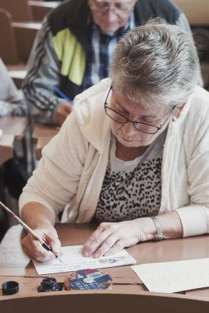 Vanhempi naishenkilö kirjoittaa mustekynällä.