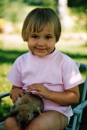 Tyttölapsi istuu kani sylissään