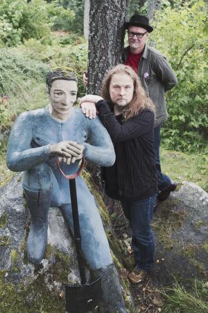 Två män och en staty som håller i en spade.