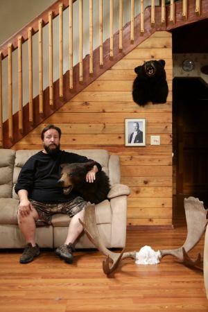 Mies kotisohvallaan, sylissä karhunpää, seinällä Kyösti Kallion kuva.