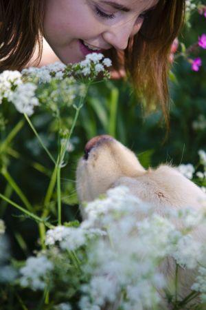 Sofia Svevar och hunden Casper i en blomsteräng
