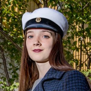 en ung kvinna som har sin nya studentmössa på sig och står på en innergård framför gula hus