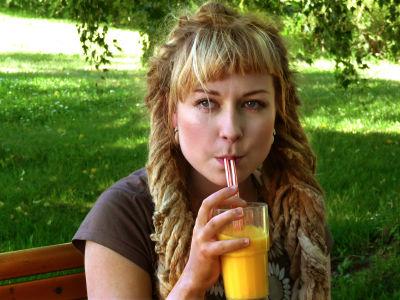 En kvinna som dricker apelsinjuice 027103f82fded