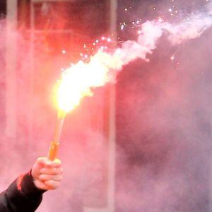 En person bränner av bengaliska eldar på en läktare.