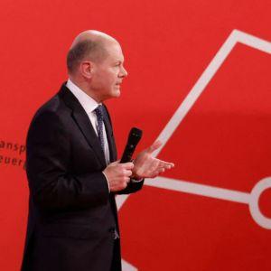Olaf scholz står på ett podium - i bakgrunden syns stora bokstäver i rött som bokstaverar SPD