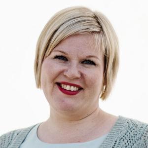 Annika Saarikko fotograferad rakt framifrån. Hon tittar in i kameran och ler.