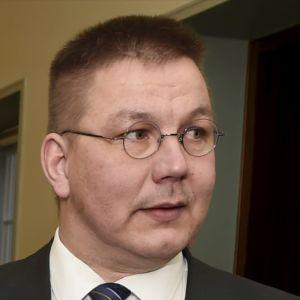 En man med glasögon och kostym i riksdagens korridor.