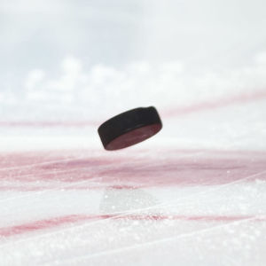 En puck studsar på isen bredvid skridskor.