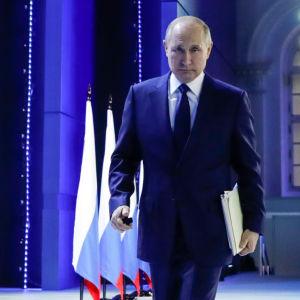 Vladimir Putin på väg bort från en talarstol. Han har ryska flaggor vid sin sida.
