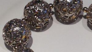 detalj av ett silverhalsband med guldinslag, halsbandet format som stora kulor.