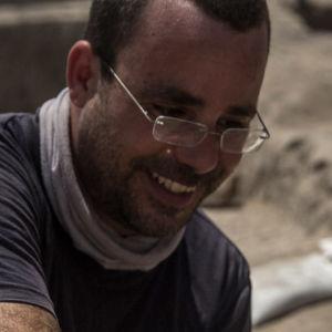 En leende man undersöker en hög med guldmynt som finns på ett bord. Mannen har glasögon och skägg och ser glad ut.